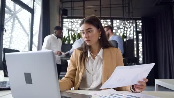 Vysoce kvalifikovaná okouzlující mladá kancelářská pracovnice zadávající údaje z různých zpráv do notebooku, sedící u svého pracovního stolu v moderní kanceláři na pozadí svých kolegů