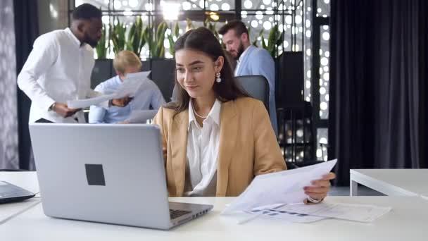 Dobře vypadající radostná kancelářská pracovnice sedící na svém pracovišti a radující se z dobrých výsledků na obrazovce počítače v moderní kanceláři