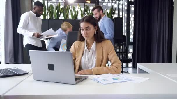 Pěkně cílevědomá mladá podnikatelka sedí na svém pracovišti s počítačem a dívá se na kameru s upřímným úsměvem v moderní kanceláři