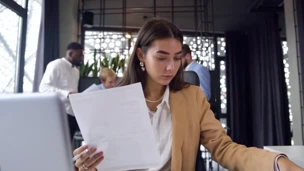 Atraktivní mladá pracovnice s různými reporty a pomocí notebooku u kancelářského stolu na pozadí svých kolegů