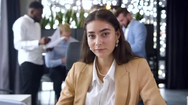 Okouzlující mladá zkušená podnikatelka sedí v moderní kanceláři a ukazuje ok znamení na kameře