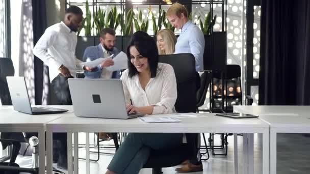 Fiatal, kellemes, magabiztos üzletasszony mosolyog, miközben a laptopján dolgozik az irodai szobában
