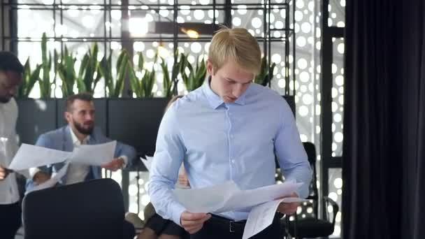 Atraktivní portrét seriózního mladého blonďatého podnikatele, který se blíží ke svému pracovišti a začíná pracovat s počítačem na pozadí spolupracovníků