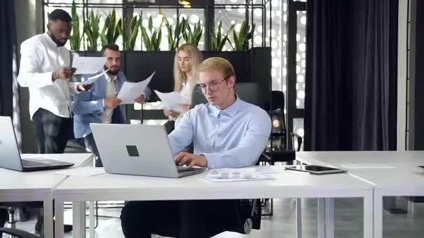 Detailní záběr pohledný mladý byznysmen v brýlích pracuje na notebooku v moderní kanceláři se svými kolegy