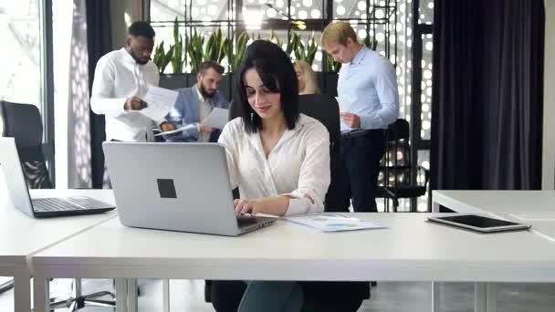 Zaměřeno dobře vypadající brunetka kancelářský pracovník psaní na notebooku v moderní kanceláři na pozadí firemních spolupracovníků