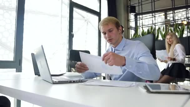 Attractive portrait of handsome young blond businessman analising report with charts with datas on laptop at his workplace in the office room