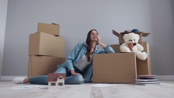 Müde schöne 30-jährige Mädchen mit langen Haaren und in stilvoller Kleidung, die nach dem Umzug in die neue Wohnung auf der Loge ruht