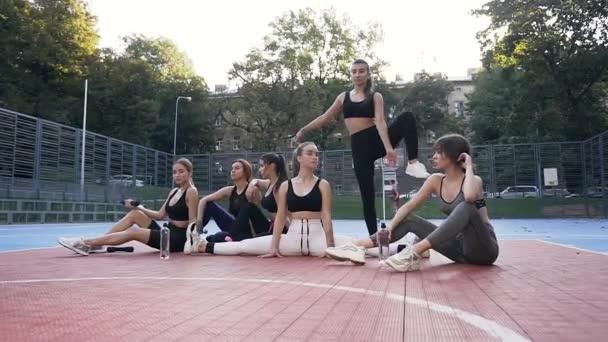 ein sportliches junges Mädchen beim vertikalen Binden zwischen ihren fitten Freundinnen im Freiluftstadion