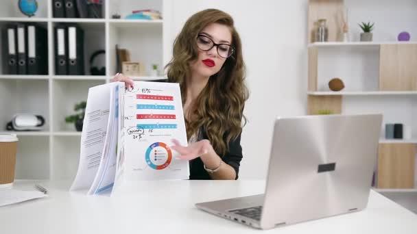 Attraktive hochqualifizierte, kluge und zielgerichtete junge Bürokauffrau präsentiert sich per Videoanruf in ihrem modernen Büro