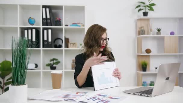 Sympatické vysoce kvalifikované sebevědomé mladé obchodní dáma v brýlích a stylové oblečení prezentovat finanční diagram během videokonference se svým obchodním partnerem