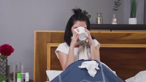 Kranke müde Frau trinkt Tee, während sie sich bei hohen Temperaturen und Husten schlecht fühlt, während sie zu Hause gegen Grippe oder Angina behandelt wird