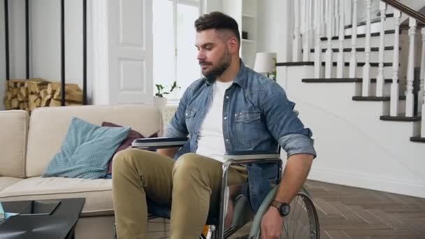 Schöner selbstbewusster, friedlicher junger bärtiger Mann im Rollstuhl, der von zu Hause aus am Computer seine Arbeit aufnimmt