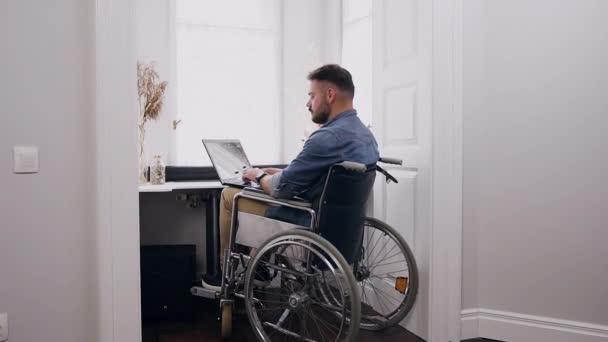 Hübscher, selbstbewusster, bärtiger 30-jähriger Mann im Rollstuhl arbeitet zu Hause am Laptop neben dem Fenster