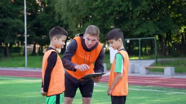 Front view of confident experienced young football coach which explaining the scheme of game to his football pupils during training day on soccer field ,4k