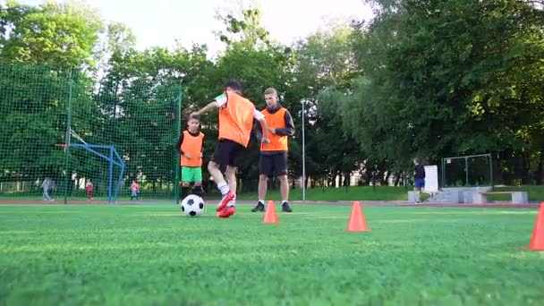 Good-looking high-skilled young football instructor watching how his teen pupils doing running exercises with ball using obstacles during training on the outdoors sport field
