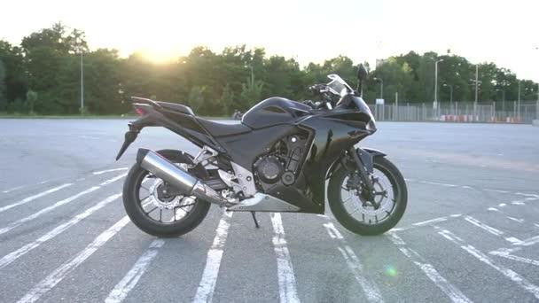 Zblízka luxusní drahé černé motorce, která stojí na sportovním hřišti ve světle slunečních paprsků