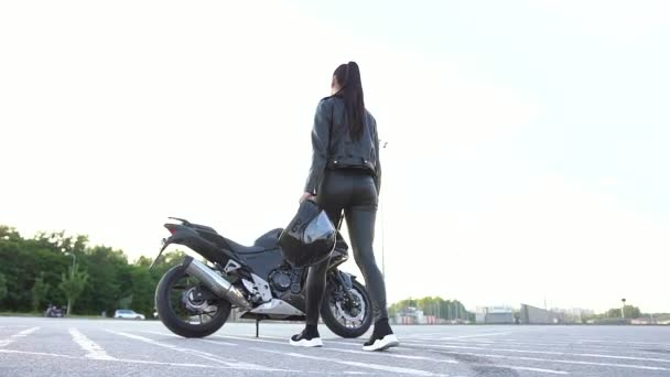Back view of gorgeous sexy young stylish female biker with helmet in hands which coming up and getting on luxurious motorbike,looking at camera with nice smile