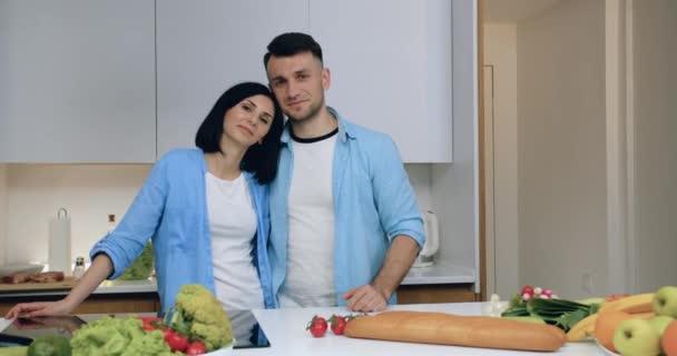 Jóképű modern boldog mosolygós házaspár szerelmes álló konyha háttér és pózol a kamera