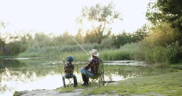 Portré a vonzó öreg szakállas halászról szalmakalapban és a 10 éves unokájáról, akik együtt horgásztak a tavon a nyári reggelen.