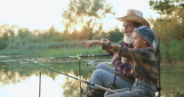Schöne lächelnde glückliche kleine Junge angeln in der Nähe Teich zusammen mit seinem selbstbewussten reifen bärtigen Opa und trinken mit ihm heißen Tee bei Sonnenuntergang, Zeitlupe