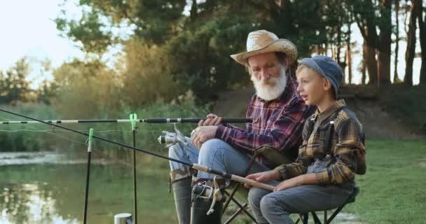 Oldalnézet boldog pozitív kisfiú, amely halászat együtt a vonzó szakállas nagyapa a tavon, és elmondja az álmát a nagy hal