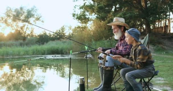 Csodálatos pillanatok a családi kikapcsolódásra, ahol a szerethető, elismert szakállas nagyapa és engedelmes kis unokája botokat dobálnak a tóba a közös horgászat során naplementekor.