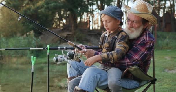 Oldalnézet vonzó magabiztos idős szakállas nagyapa, amely megtanítja az érdeklődő kötelességtudó unoka, hogyan kell használni rúd tekercs közös halászat során a tó közelében