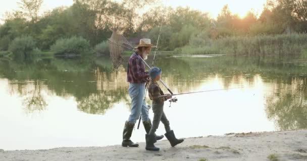 Portrét půvabné přátelské rodiny starého vousatého dědečka a jeho malého zvědavého vnoučete, který nese rybářské náčiní na ramenou a jde rybařit k rybníku
