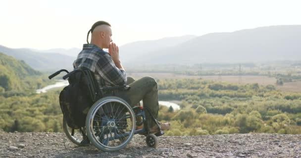 Seitenansicht des hübschen ruhigen konzentrierten Mannes mit kleinem Pferdeschwanz, der im Rollstuhl auf dem Hügel sitzt und betet