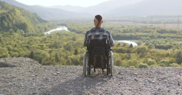 Rückansicht eines gut aussehenden modernen Behinderten im Rollstuhl, der die malerische Natur vom Hügel aus betrachtet