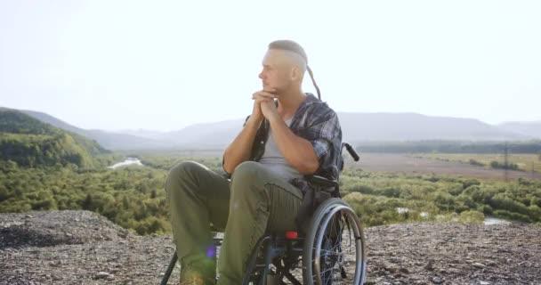 Nahaufnahme eines attraktiven, verträumten jungen Behinderten im Rollstuhl, der morgens auf dem Hügel vor der schönen Naturkulisse an sein Leben nach einem Unfall oder einer Krankheit denkt