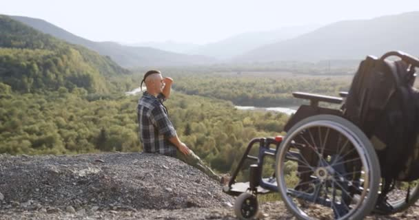 Seitenansicht von gutmütigen fröhlichen fröhlichen behinderten Kerl, der auf den Hügeln Stein sitzt und in die Ferne schaut und die wunderbare Natur genießt
