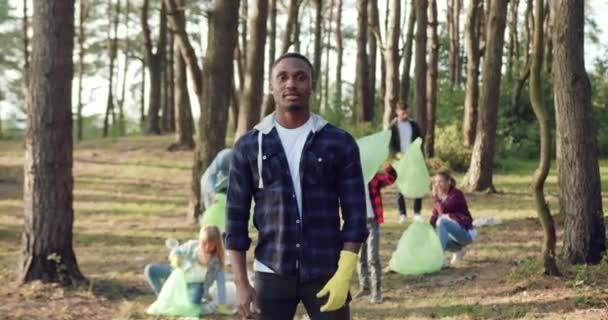 Příjemný spokojený aktivní afroameričan stojící před kamerou poblíž svých přátel - členů komunity milovníků přírody, kteří sbírají do igelitových pytlů odpadky z lesního území