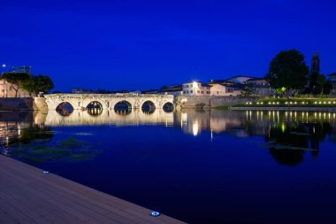 Roman stone bridge Tiberius with city lights reflecting in the water. Rimini, Italy.