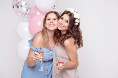 Two smiling girlfriends celebrating with wineglasses and hugging with balloons on backgropund , bachelorette party