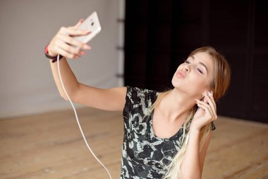 Young woman happy takes a selfie while listening music sitting on the floor with earphones.