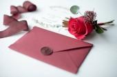 Invito come una lettera decorata su una tovaglia bianca con una composizione floreale di nozze