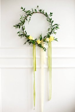 Beautiful hand made everlasting dry wreath made of nartsyss, colourful feathers and eucalyptus on the white wall background