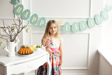 Attractive little girl in a colorful dress posing and smiling against the background of a decorated Easter cake and eggs