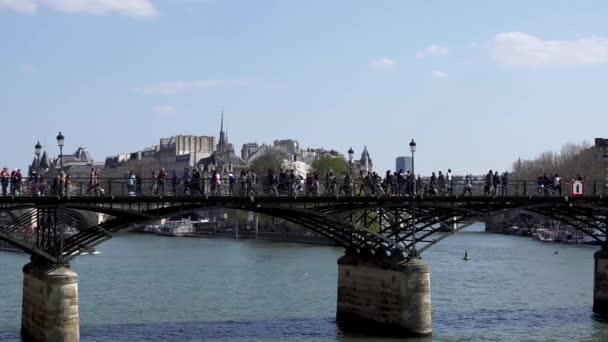 People walking on Pont des Arts bridge on the Seine river - Paris
