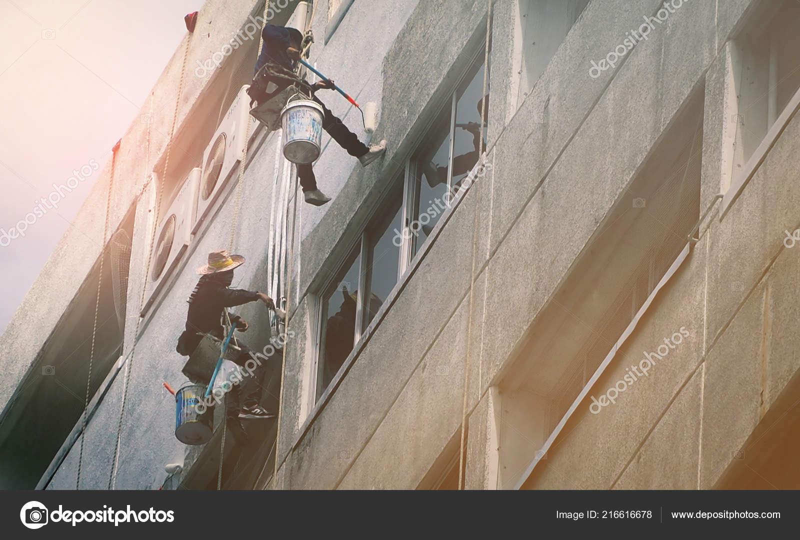 絵画壁高層建物の労働者のチーム 画家は ローラーでオフィスビル