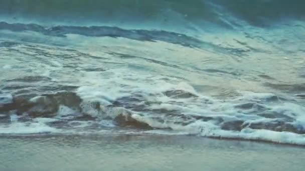 Slow motion of ripple wave at seashore. Clear water and Sand beach in the morning at coastline. Beautiful coast. Summer vacation at tropical paradise sea beach. Peaceful and tranquil concept.