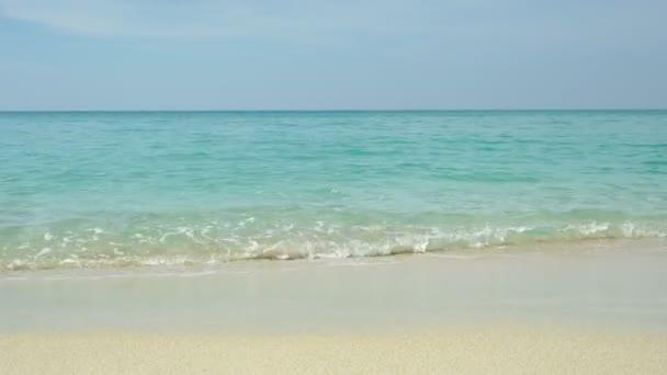 Písečná pláž ráno s zvlnění vlny na pobřeží proti modré obloze bílé mraky. Krásné Azurové pobřeží slunečného dne. Letní dovolená na pláži tropického ráje.