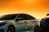 Front View fehér autó luxus és modern design parkolt a parkolóban, gyönyörű narancs és arany naplemente ég. Autóipar. Közúti utazás utazás. Fényes fehér autó hátteret Autóápolási