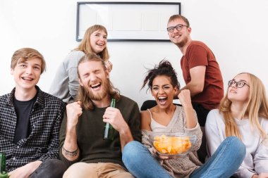 Group of joyful friends sitting on sofa and watching film together with chips and beer at home