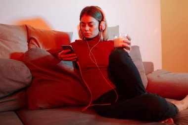 Young lady in headphones sitting on sofa with glass of milk and cellphone in hands. Cool girl listening music while spending time at home stock vector