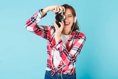 Portrait of young lady in headphones looking in little retro camera while taking photo on over pink background