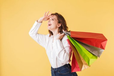 Portrait of young cheerful lady in shirt and denim shorts standing with colorful shopping bags in hands and happily looking aside on over pink background