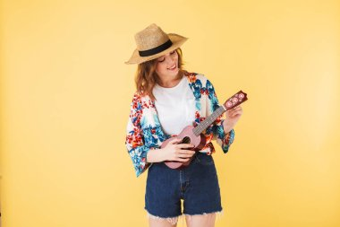 Portrait of young pretty lady in straw hat and colorful shirt standing with little guitar and happily playing on it on over pink background