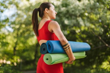 Photo of young pretty woman in red jumpsuit standing from back with colorful yoga mats in hands in park